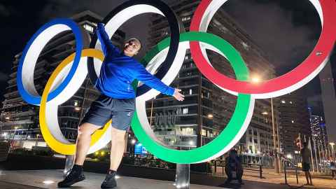 Kanah Andrews-Nahu standing in front of the Olympic rings in Tokyo.