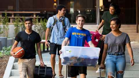 students with luggage moving into residence