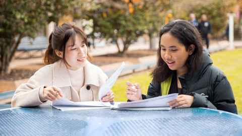 Two students sitting outside at a table with documents