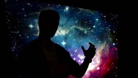 Physics student silhouetted against and image of space.