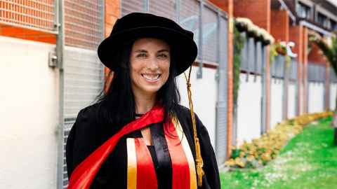 Woman in motarboard and graduation gown with red PhD scarf