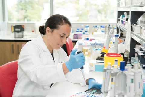 Woman sitting at a desk in a lab filling a tray with a pipette