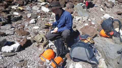 PhD student Geoff Lerner studying volcanic rock.