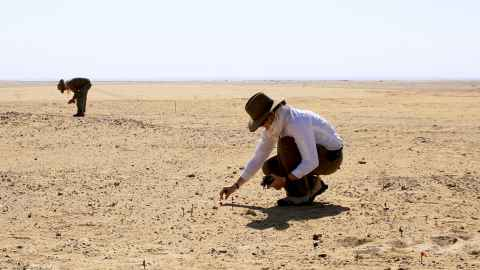 Environment scientists in a desert taking measurements