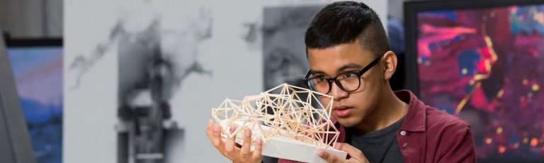 A student looking at a building truss model