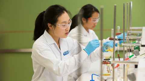 Two students doing chemical titration at the lab.